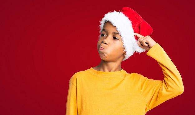 Menino afro-americano com chapéu de natal com dúvidas e com a expressão do rosto confuso sobre fundo vermelho Foto Premium