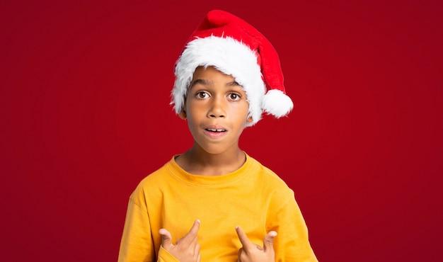 Menino afro-americano com chapéu de natal com expressão facial de surpresa sobre parede vermelha Foto Premium