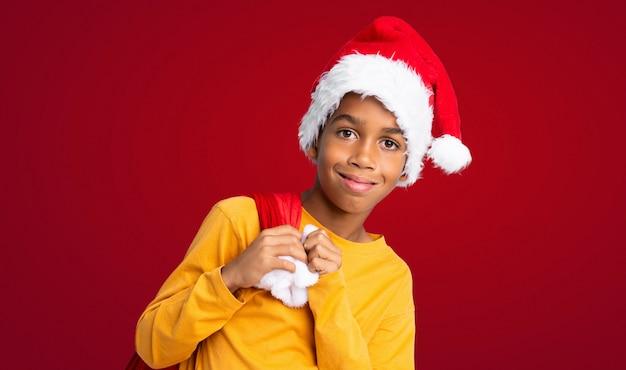 Menino afro-americano com chapéu de natal e levar uma sacola com presentes ao longo da parede vermelha Foto Premium