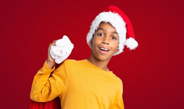 Menino afro-americano com chapéu de natal e levar uma sacola com presentes e fazendo o gesto de surpresa sobre fundo vermelho Foto Premium