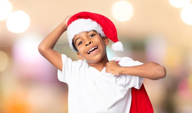 Menino afro-americano com chapéu de natal e levar uma sacola com presentes sobre fundo desfocado Foto Premium