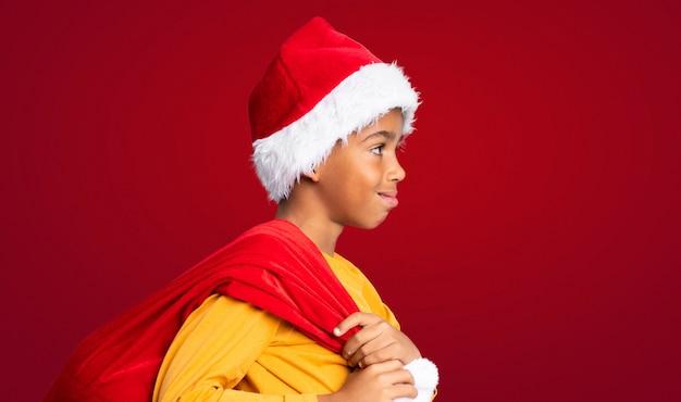 Menino afro-americano com chapéu de natal e levar uma sacola com presentes sobre fundo vermelho Foto Premium