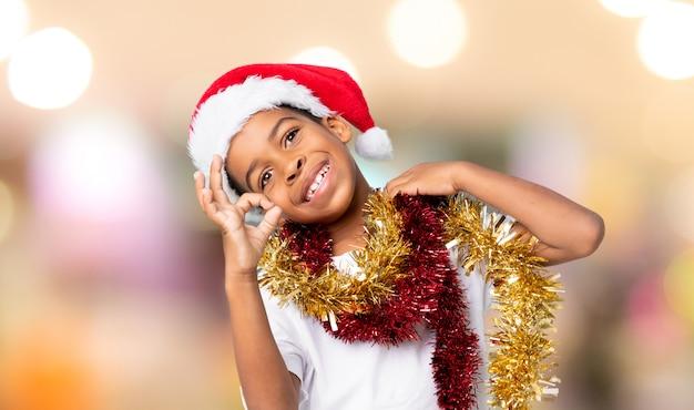 Menino afro-americano com chapéu de natal, mostrando sinal de ok com os dedos sobre fundo desfocado Foto Premium