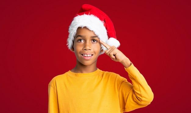 Menino afro-americano com chapéu de natal, pretendendo realizar a solução sobre fundo vermelho Foto Premium