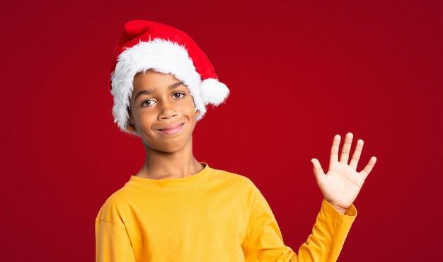 Menino afro-americano com chapéu de natal saudando com a mão com expressão feliz sobre fundo vermelho Foto Premium