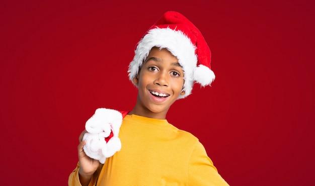 Menino afro-americano com chapéu de natal sobre fundo vermelho Foto Premium