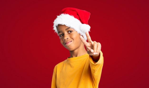 Menino afro-americano com chapéu de natal sorrindo e mostrando sinal de vitória sobre fundo vermelho Foto Premium