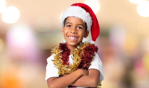 Menino afro-americano com chapéu de natal sorrindo muito sobre fundo desfocado Foto Premium