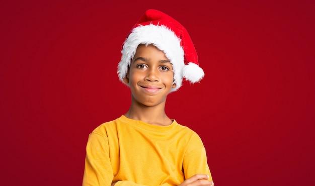 Menino afro-americano com chapéu de natal sorrindo muito sobre parede vermelha Foto Premium