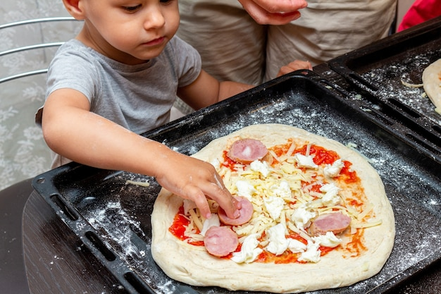Menino ajudando a mãe a fazer pizza em casa Foto Premium