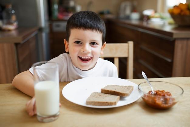 Menino alegre brincando enquanto come Foto gratuita