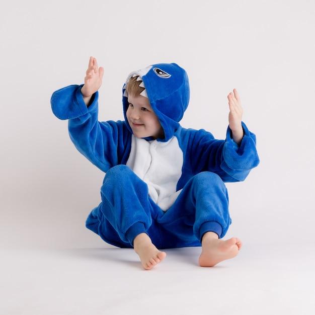 Menino alegre posando em um fundo branco em traje de pijama, tubarão azul Foto Premium