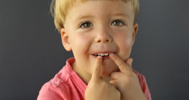 Menino aponta os dedos das duas mãos nos dentes Foto Premium