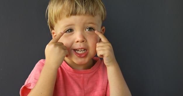 Menino aponta os dedos das duas mãos nos olhos Foto Premium