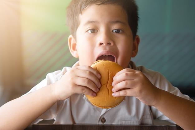Menino asiático do retrato que come um hamburger. conceito de saúde. Foto Premium