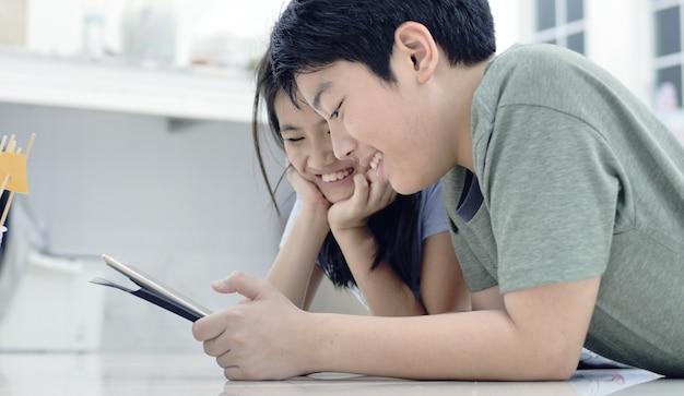Menino asiático e menina que jogam o jogo no telefone celular junto com a face do sorriso. Foto Premium