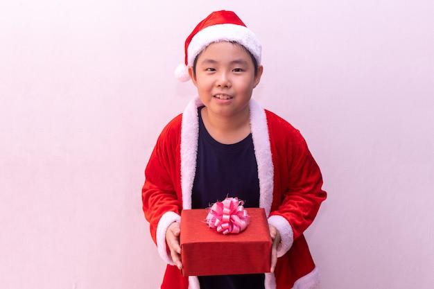 Menino asiático, em, papai noel, roupas, segurando, presente Foto Premium