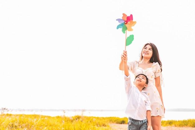 Menino asiático pequeno e sua mamã que jogam a turbina colorida do arco-íris no prado. Foto Premium