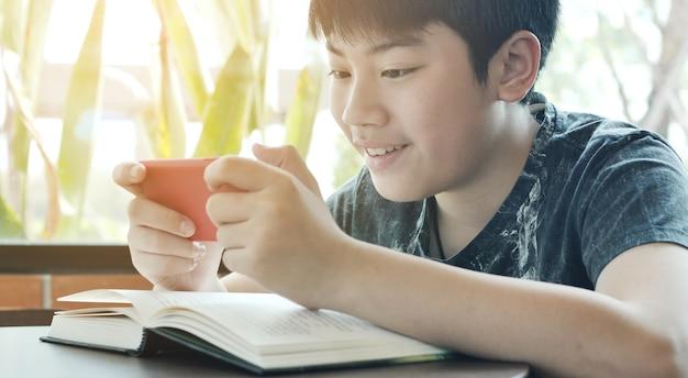 Menino asiático que joga o jogo móvel no telefone esperto junto. Foto Premium