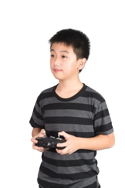 Menino asiático, segurando, rádio controle remoto, handset, para, helicóptero, drone, ou, avião Foto Premium