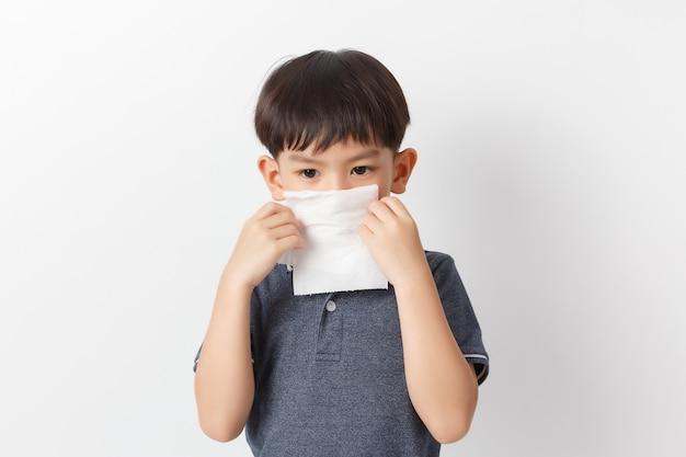Menino asiático segurando um lenço de papel e assoar o nariz. garoto com rinite fria. Foto Premium