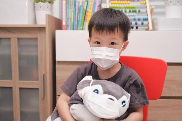 Menino asiático triste e seu brinquedo de pelúcia de cachorro com máscaras médicas protetoras e máscaras faciais Foto Premium