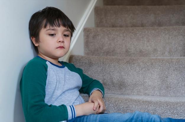 Menino asiático triste sentado sozinho na escada pela manhã, criança solitária com cara triste e não feliz por voltar para a escola, menino criança deprimida sentado no canto de uma escada, saúde mental Foto Premium
