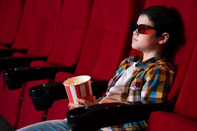 Menino assistindo filme no cinema Foto gratuita