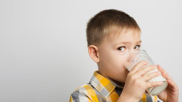 Menino bebendo leite com copo Foto gratuita