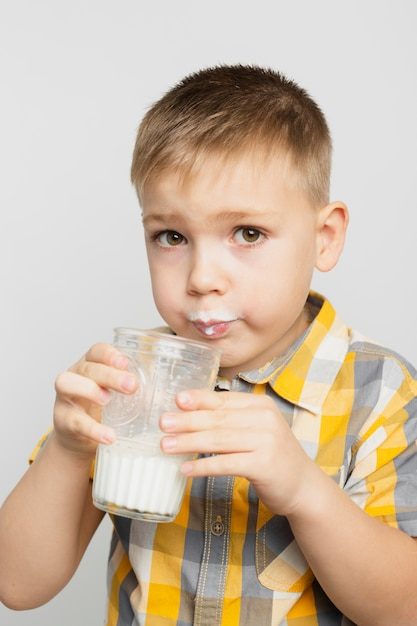 Menino bebendo leite de vidro Foto gratuita