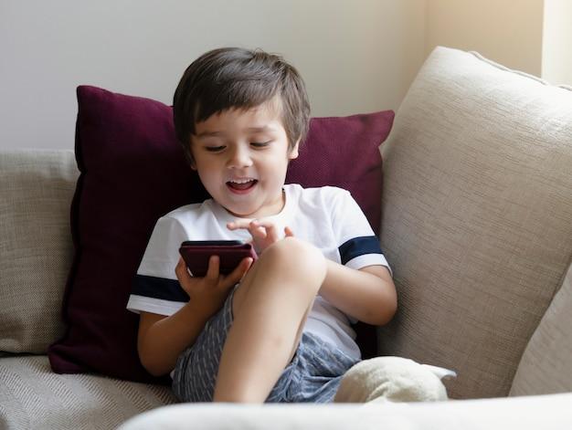 Menino bonitinho assistindo desenhos no celular Foto Premium