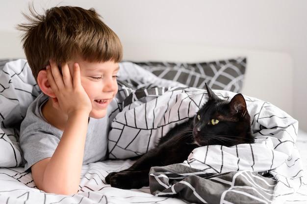 Menino bonitinho assistindo seu gato Foto Premium