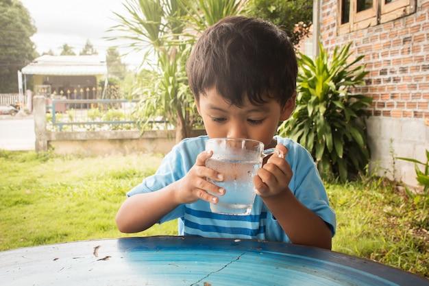 Menino bonitinho bebendo água no parque Foto Premium