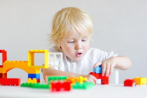 Menino bonitinho brincando com blocos de plástico coloridos dentro de casa Foto Premium