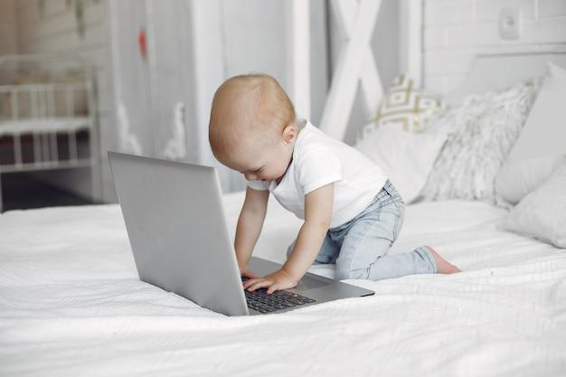 Menino bonitinho brincando com um laptop em uma cama Foto gratuita