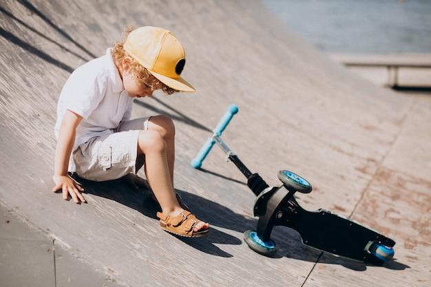 Menino bonitinho com cabelo encaracolado, scooter Foto gratuita
