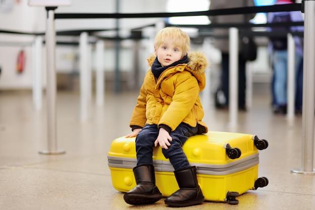 Menino bonitinho com grande mala amarela no aeroporto internacional antes do voo Foto Premium