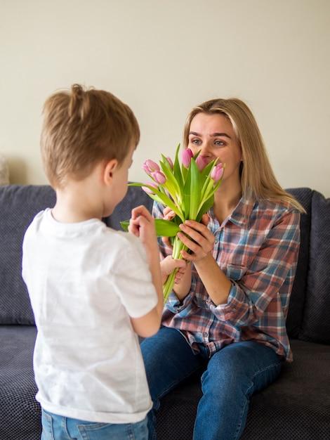 Menino bonitinho dando flores para sua mãe Foto gratuita