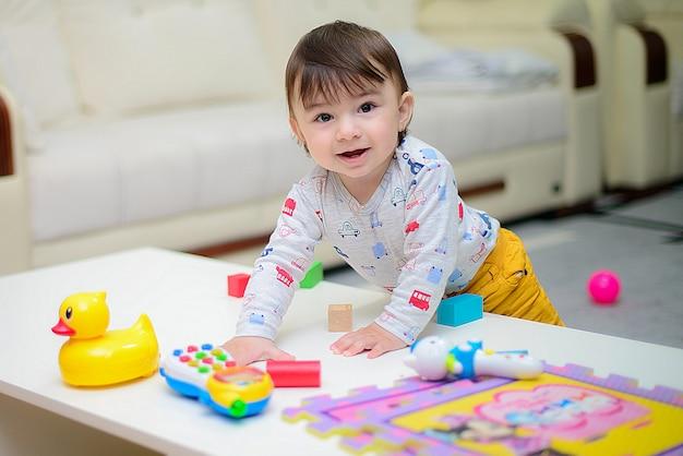 Menino bonitinho desfrutando enquanto brincava com brinquedos ou blocos no quarto Foto Premium