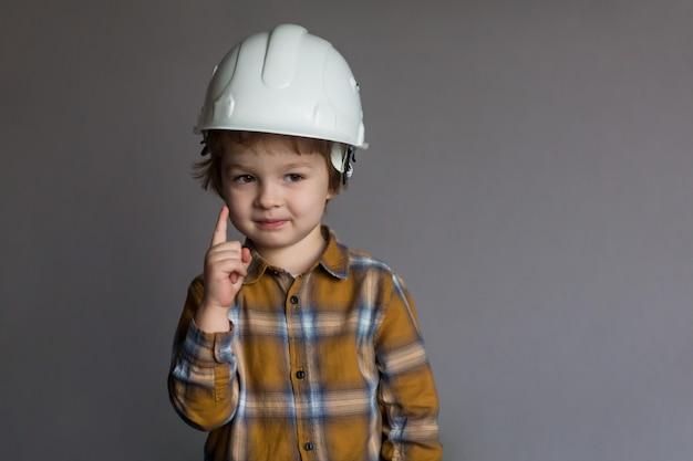 Menino bonitinho em um capacete, construção e conceito arquitetônico Foto Premium