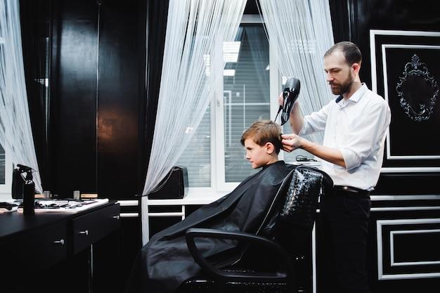 Menino bonitinho está cortando cabelo de cabeleireiro Foto Premium