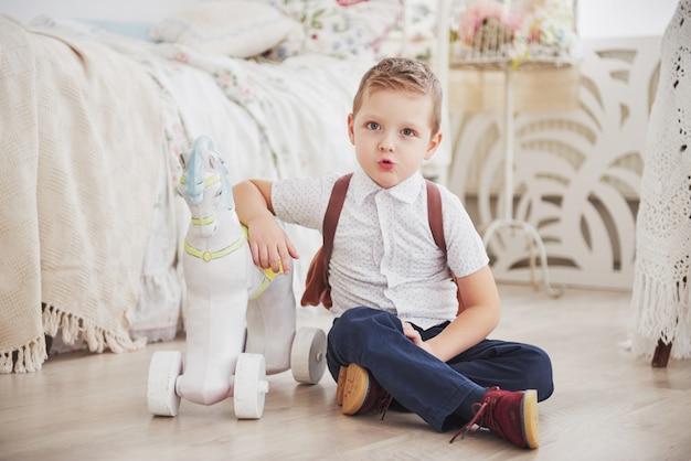 Menino bonitinho está indo para a escola pela primeira vez. criança com mochila e livro. garoto faz uma maleta, quarto de criança em um plano de fundo. de volta à escola Foto Premium