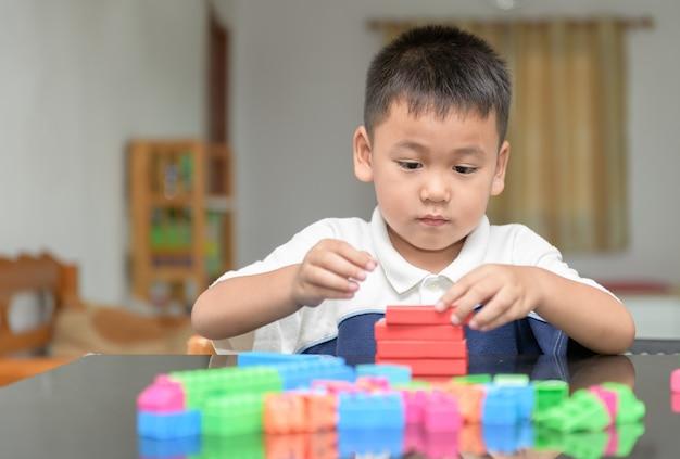 Menino bonitinho está jogando tijolo de madeira Foto Premium