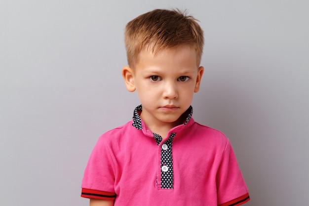 Menino bonitinho na camiseta rosa posando contra fundo cinza Foto Premium