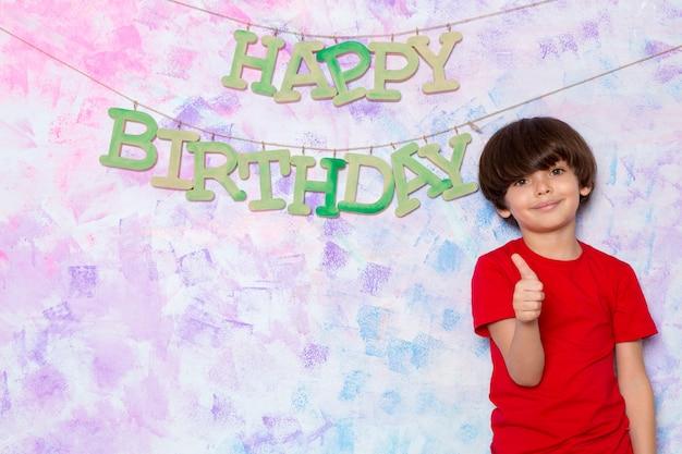 Menino bonitinho na camiseta vermelha, decorar a parede colorida com palavras de feliz aniversário Foto gratuita
