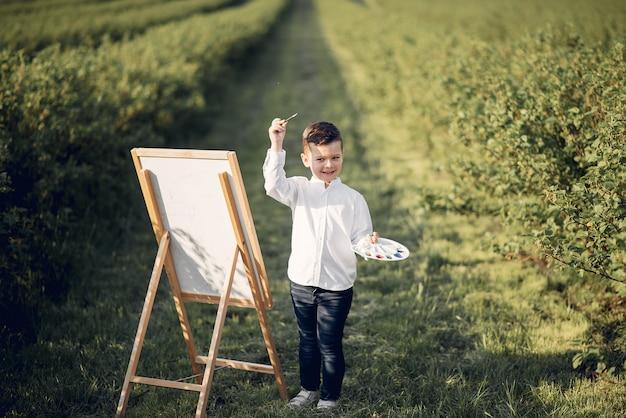Menino bonitinho pintura em um parque Foto gratuita