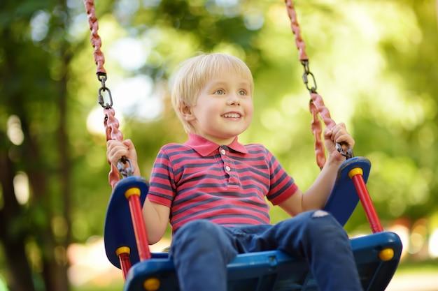 Menino bonitinho se divertindo no playground ao ar livre. criança no balanço Foto Premium
