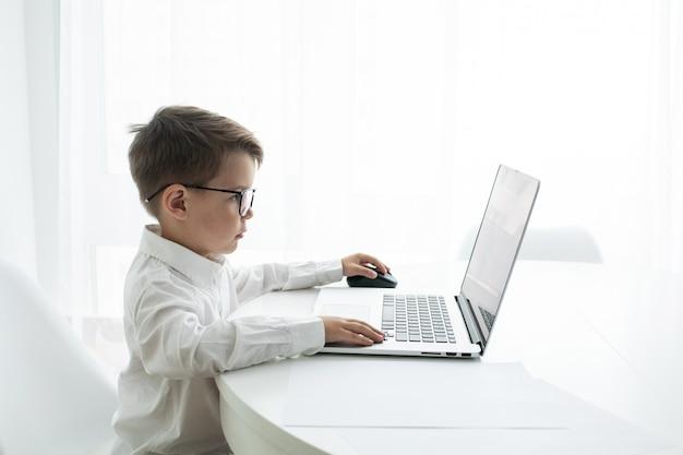 Menino bonitinho usando laptop enquanto faz lição de casa contra branco Foto Premium