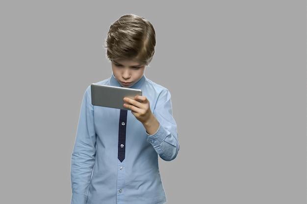 Menino bonito caucasiano usando smartphone. menino olhando para o celular em fundo cinza. conceito de lazer, crianças, tecnologia, vício em internet e pessoas. Foto Premium