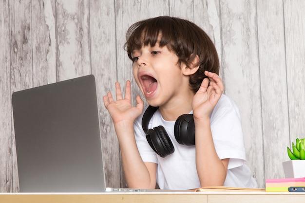 Menino bonito criança em fones de ouvido de camiseta branca preta usando laptop cinza em cima da mesa junto com planta verde Foto gratuita